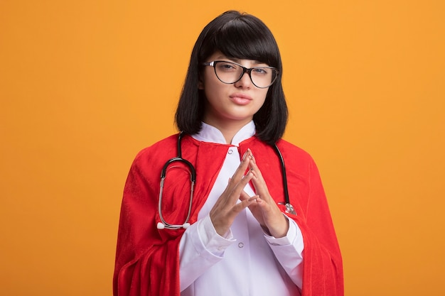Przekonana, młoda dziewczyna superbohatera w stetoskopie z szlafrokiem i płaszczem w okularach, trzymając się za ręce razem