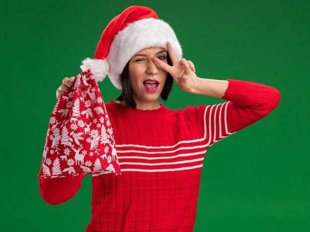 Przekonana, młoda dziewczyna w kapeluszu santa trzymająca worek na prezent świąteczny, patrząc na kamerę mrugającą pokazując symbol znaku v w pobliżu oka na białym tle na zielonym tle