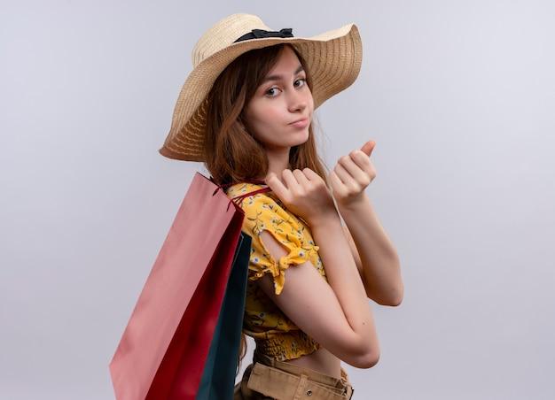 Przekonana, młoda dziewczyna w kapeluszu, trzymając papierowe torby, stojąc w widoku profilu na na białym tle