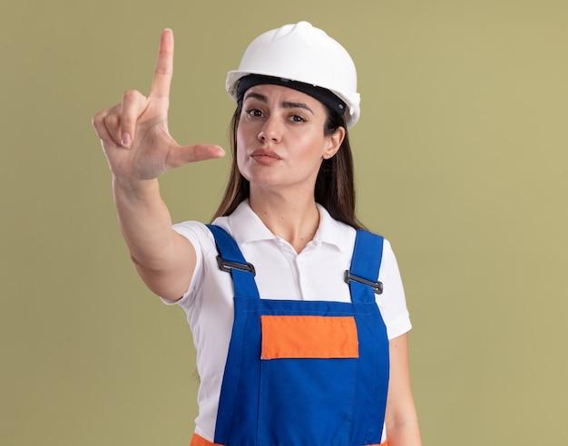 Przekonana, młoda kobieta budowniczy w mundurze pokazujący przegrany gest na białym tle na oliwkowej ścianie
