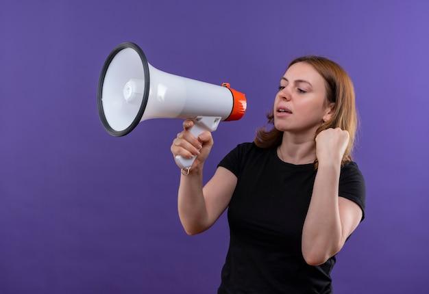 Przekonana, młoda kobieta dorywczo rozmawia przez głośnik z podniesioną pięścią na odosobnionej fioletowej przestrzeni