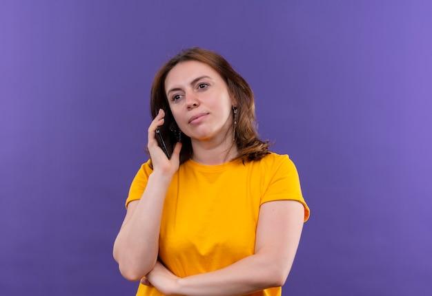 Przekonana, młoda kobieta dorywczo rozmawia przez telefon na odosobnionej fioletowej przestrzeni z miejsca na kopię