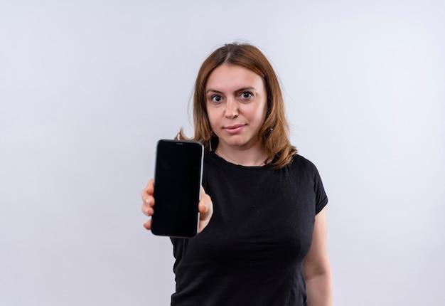 Przekonana, młoda kobieta dorywczo wyciągając telefon komórkowy na odosobnionej białej przestrzeni z miejsca na kopię