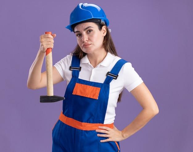 Przekonana, młoda kobieta konstruktora w mundurze trzymając młotek, kładąc rękę na biodrze na białym tle na fioletowej ścianie