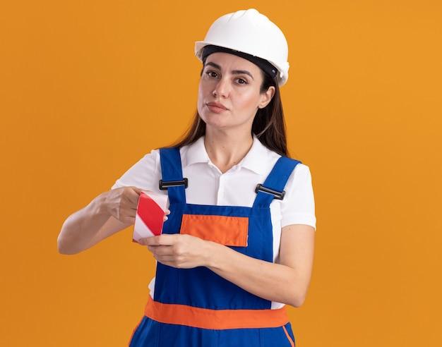 Przekonana, młoda kobieta konstruktora w mundurze, trzymając taśmę izolacyjną na pomarańczowej ścianie