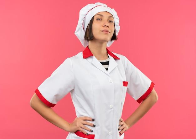 Przekonana, młoda kobieta kucharz w mundurze szefa kuchni kładąc ręce na talii na różowym tle
