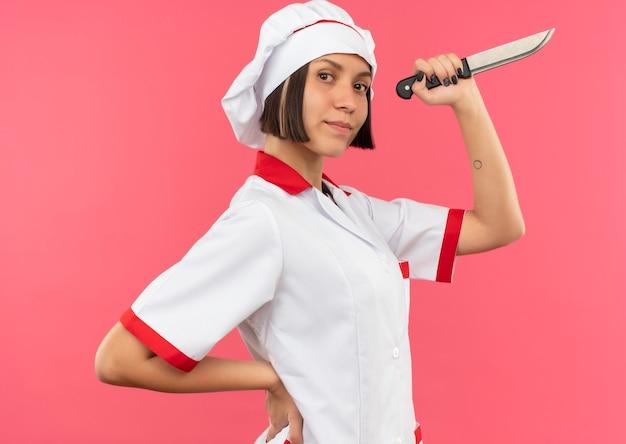 Przekonana, młoda kobieta kucharz w mundurze szefa kuchni stojącej w widoku profilu, kładąc rękę na talii i trzymając nóż na różowym tle