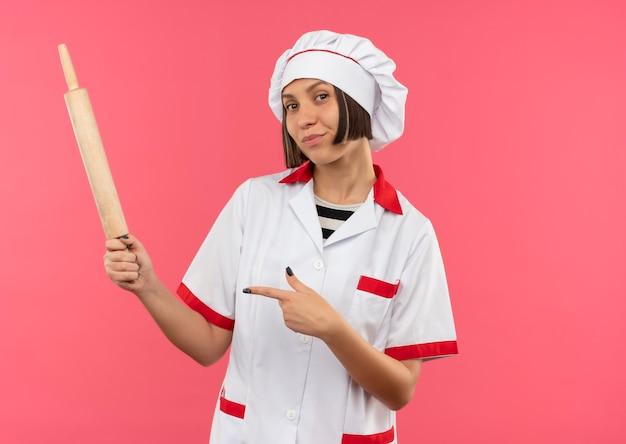 Przekonana, młoda kobieta kucharz w mundurze szefa kuchni, trzymając i wskazując wałek do ciasta na różowym tle z miejsca na kopię