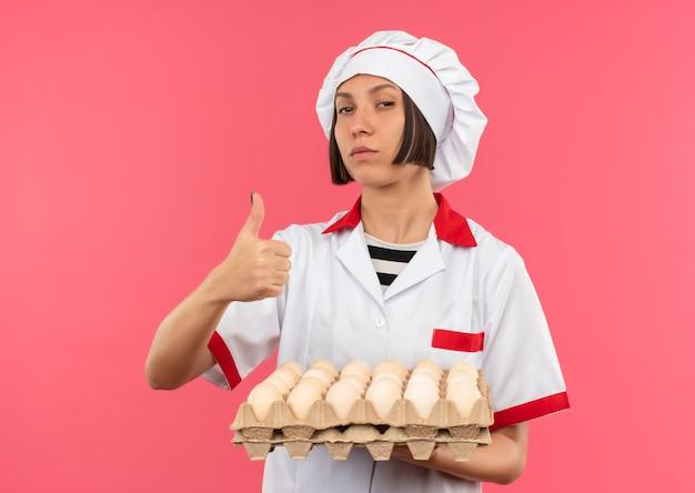 Przekonana, młoda kobieta kucharz w mundurze szefa kuchni, trzymając karton jaj i pokazując kciuk do góry na różowym tle