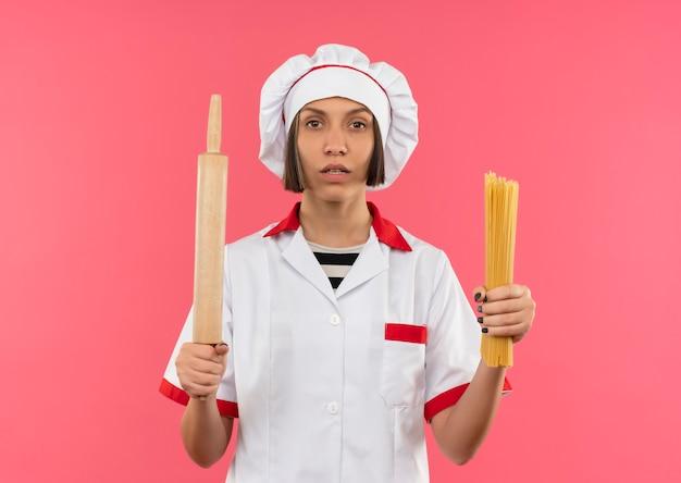 Przekonana, młoda kobieta kucharz w mundurze szefa kuchni, trzymając makaron spaghetti i wałkiem do ciasta i patrząc na różowym tle