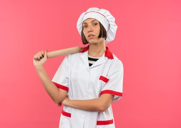 Przekonana, młoda kobieta kucharz w mundurze szefa kuchni trzymając wałek do ciasta, patrząc na różowym tle z miejsca na kopię