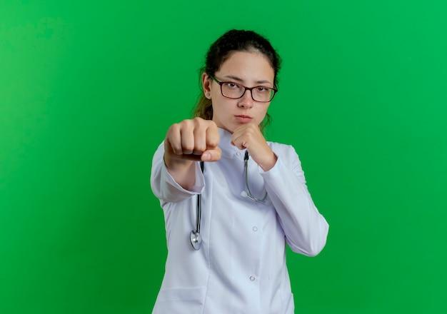 Przekonana, młoda kobieta lekarz ubrana w medyczny szlafrok i stetoskop i okulary robi gest boksu na białym tle na zielonej ścianie z miejsca na kopię