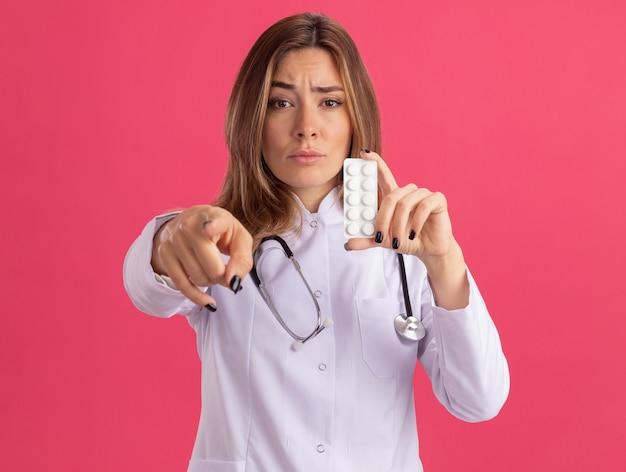 Przekonana, młoda kobieta lekarz ubrana w szlafrok medyczny ze stetoskopem, trzymając punkty pigułki z przodu na białym tle na różowej ścianie