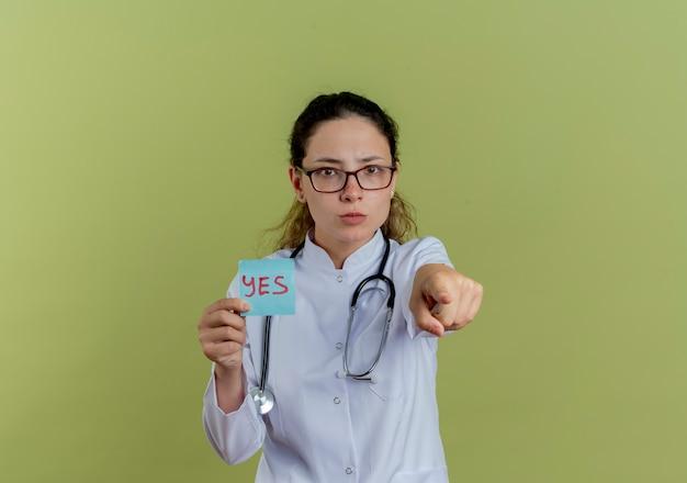 Przekonana, młoda kobieta lekarz ubrany w medyczny szlafrok i stetoskop w okularach, trzymając papierowe punkty notatki na białym tle