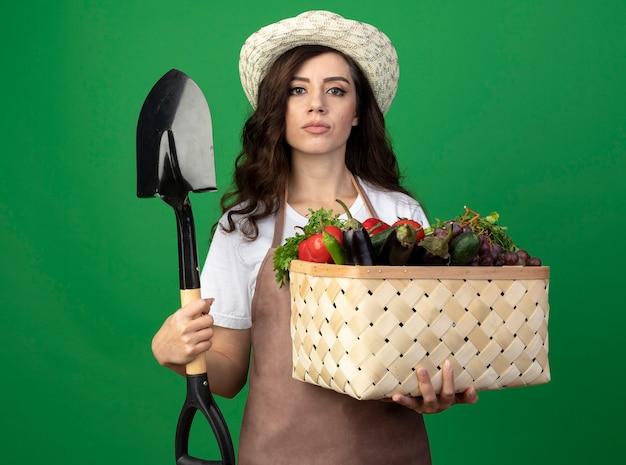 Przekonana, młoda kobieta ogrodnik w mundurze na sobie kapelusz ogrodniczy trzyma kosz warzyw i łopatę na białym tle na zielonej ścianie z miejsca na kopię