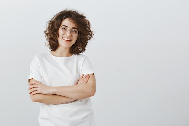 Przekonana, młoda kobieta pracująca w zespole, skrzyżowane ramiona w klatce piersiowej i uśmiechnięty zadowolony