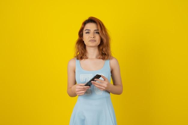 Przekonana, młoda kobieta trzymając telefon i patrząc na kamery.