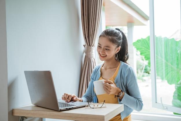 Przekonana, młoda kobieta w elegancki casual pracy na laptopie, siedząc w pobliżu okna w domu
