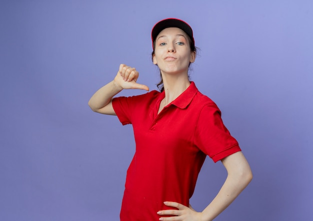 Przekonana, młoda ładna dziewczyna dostawy ubrana w czerwony mundur i czapkę, kładąc rękę na talii i wskazując na siebie na białym tle na fioletowym tle z miejsca na kopię