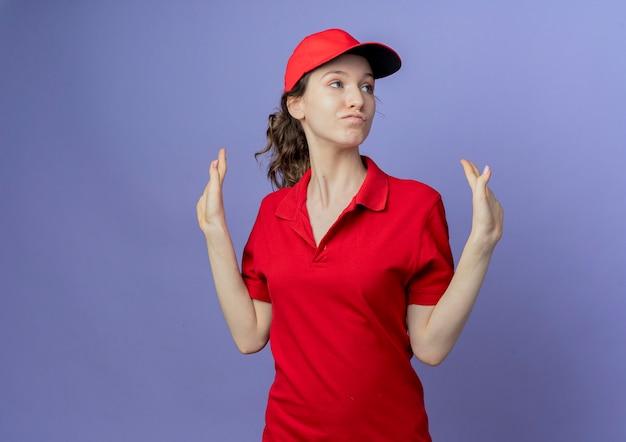 Przekonana, młoda ładna dziewczyna dostawy ubrana w czerwony mundur i czapkę, patrząc na bok, pokazując puste ręce na białym tle na fioletowym tle z miejsca na kopię