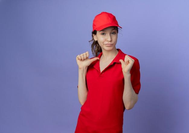 Przekonana, młoda ładna dziewczyna dostawy ubrana w czerwony mundur i czapkę, wskazując na siebie na białym tle na fioletowym tle z miejsca na kopię