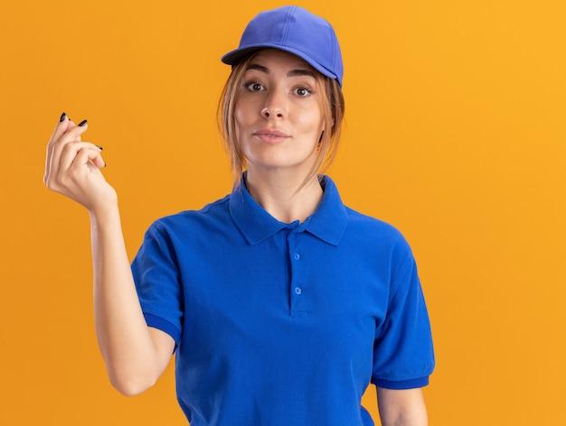 Przekonana, młoda ładna dziewczyna dostawy w mundurze gestów pieniądze ręka znak na pomarańczowo