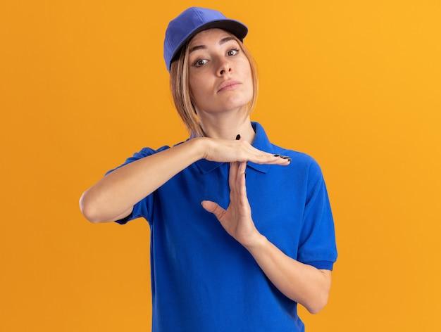 Przekonana, młoda ładna dziewczyna dostawy w mundurze gestów przekroczyła limit czasu znak na pomarańczowo