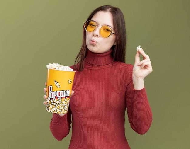 Przekonana, młoda ładna dziewczyna nosi okulary przeciwsłoneczne, trzymając wiadro popcornu i kawałka popcornu z zaciśniętymi ustami na białym tle na oliwkowozielonej ścianie