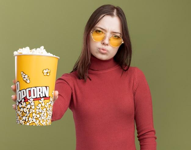 Przekonana, młoda ładna dziewczyna nosi okulary przeciwsłoneczne, wyciągając wiadro popcornu w kierunku aparatu z zaciśniętymi ustami na białym tle na oliwkowozielonej ścianie