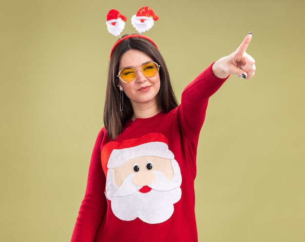 Przekonana, młoda ładna kaukaska dziewczyna ubrana w sweter świętego mikołaja i opaskę na głowę w okularach, patrząc i wskazując na bok z jednym okiem zamkniętym na białym tle na oliwkowym zielonym tle