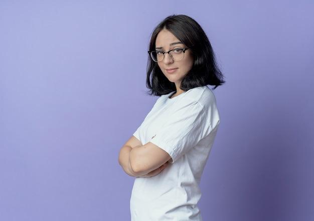 Przekonana, młoda ładna kaukaski dziewczyna w okularach stojących z zamkniętą posturą w widoku profilu na białym tle na fioletowym tle z miejsca na kopię