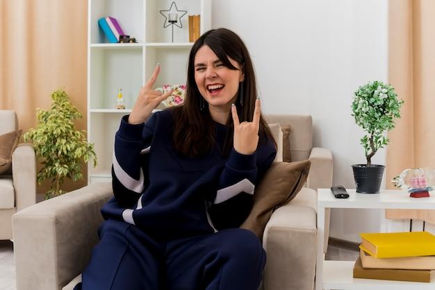 Przekonana, młoda ładna kaukaski kobieta siedzi na fotelu w zaprojektowanym salonie robi rockowy gest patrząc