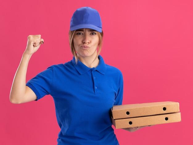 Przekonana, młoda ładna kobieta dostawy w mundurze trzyma pięść i trzyma pudełka po pizzy na białym tle