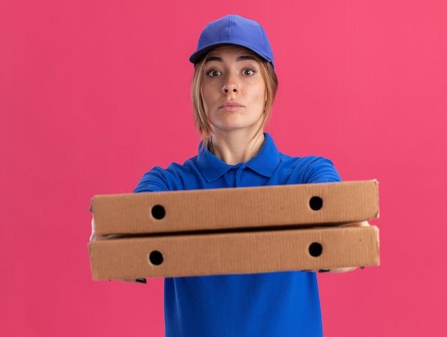 Przekonana, młoda ładna kobieta dostawy w mundurze trzyma pudełka po pizzy na białym tle
