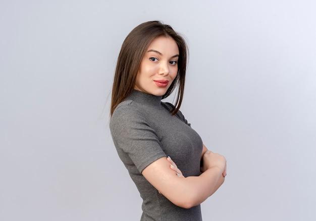 Przekonana, młoda ładna kobieta stojąca w widoku profilu z zamkniętą postawy na białym tle na białym tle z miejsca kopiowania