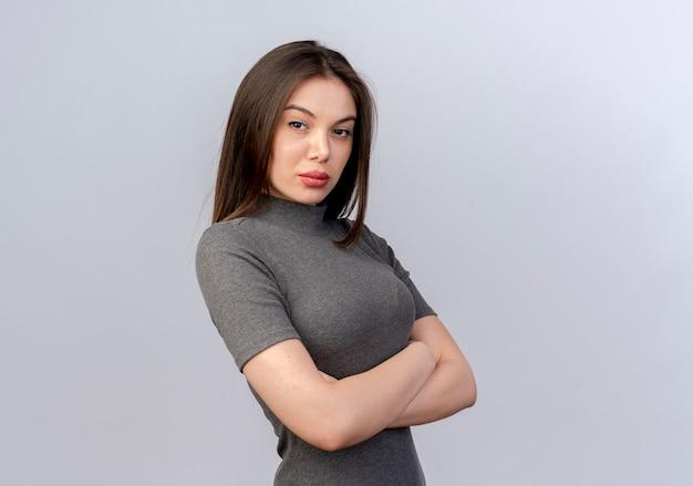 Przekonana, młoda ładna kobieta stojąca z zamkniętą postawy w widoku profilu na białym tle na białym tle z miejsca na kopię