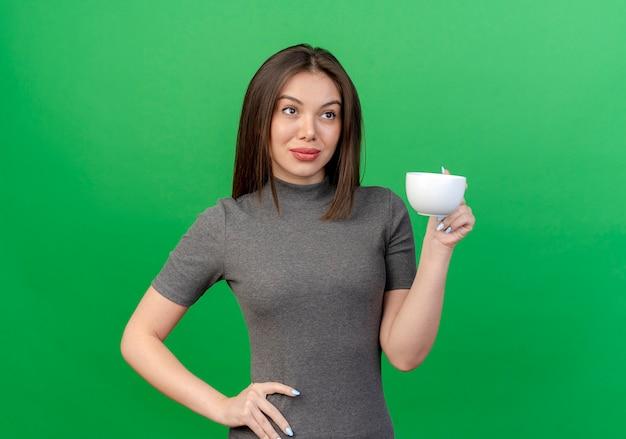 Przekonana, młoda ładna kobieta trzyma kubek kładąc rękę na talii patrząc z boku na białym tle na zielonym tle z miejsca na kopię