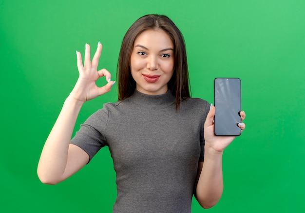 Przekonana, młoda ładna kobieta trzyma telefon komórkowy i robi ok znak na białym tle na zielonym tle