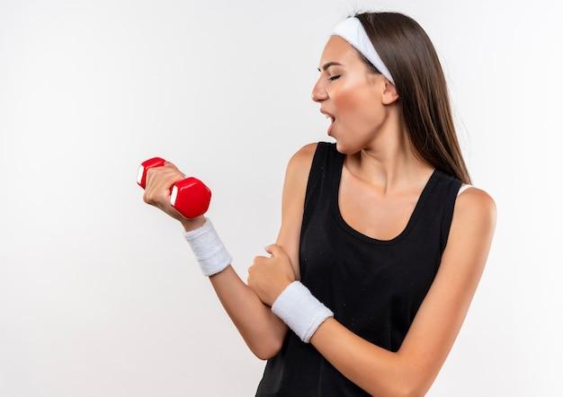 Przekonana, młoda ładna sportowa dziewczyna nosi opaskę i opaskę, trzymając i patrząc na hantle i kładąc rękę na ramieniu na białym tle na białej ścianie
