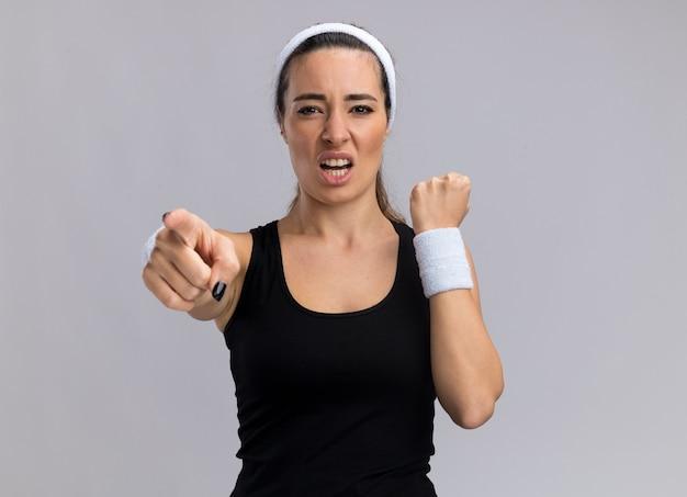 Przekonana, młoda ładna sportowa dziewczyna nosi opaskę i opaski, patrząc i wskazując zaciśniętą pięść na białym tle na białej ścianie z miejsca na kopię