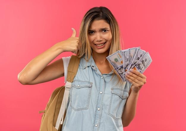Przekonana, młoda ładna studencka dziewczyna ubrana w tylną torbę, trzymając pieniądze i pokazując kciuk do góry na białym tle na różowo