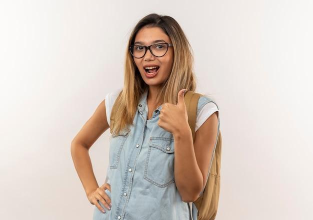 Przekonana, młoda ładna studencka dziewczyna w okularach i plecaku kładąc rękę na talii i pokazując kciuk w górę na białym tle na biały z miejsca na kopię