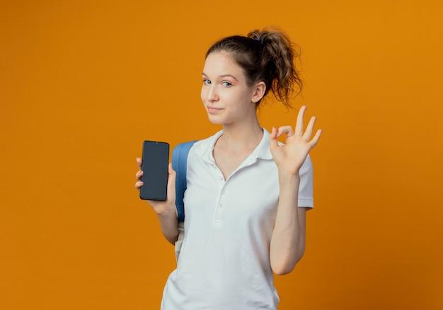 Przekonana, młoda ładna studentka na sobie tylną torbę pokazując telefon komórkowy i robi ok znak na białym tle na pomarańczowym tle z miejsca na kopię