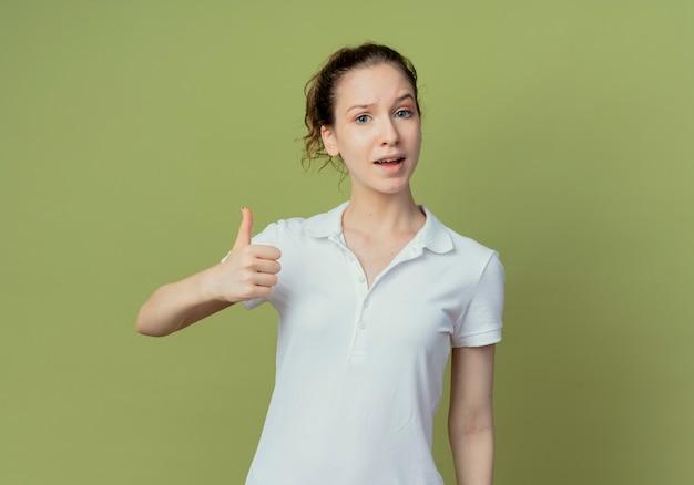 Przekonana, młoda ładna studentka pokazując kciuk do góry na aparat na białym tle na oliwkowym tle z miejsca kopiowania