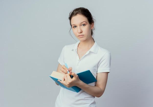 Przekonana, młoda ładna studentka trzymając otwartą książkę i pióro i patrząc na kamery na białym tle na białym tle z miejsca kopiowania