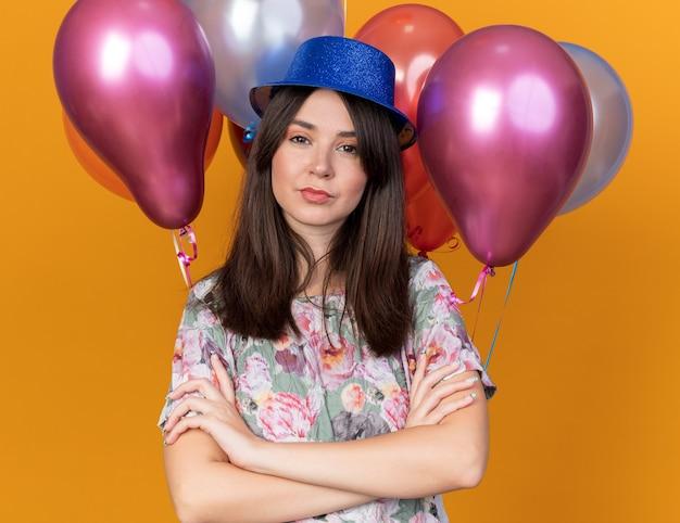 Przekonana, młoda piękna dziewczyna w kapeluszu imprezowym stojąca przed balonami krzyżującymi ręce na białym tle na pomarańczowej ścianie