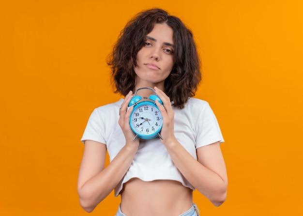 Przekonana, młoda piękna kobieta trzyma budzik na odosobnionej pomarańczowej ścianie z miejsca na kopię