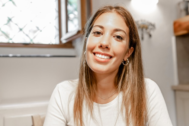 Przekonana, młoda piękna kobieta uśmiechając się, patrząc na kamery na wideokonferencję w jej domu