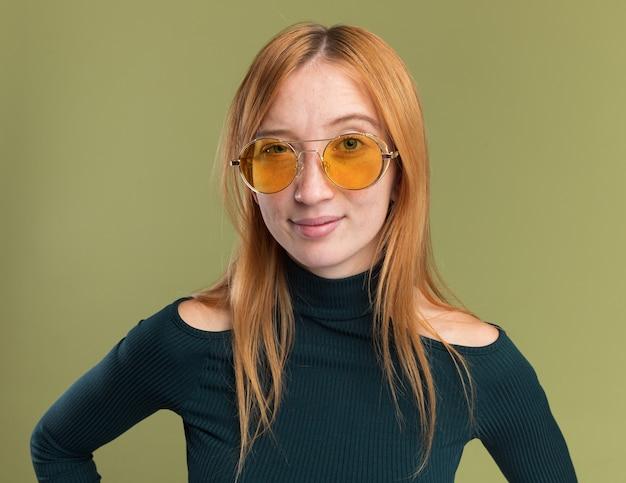 Przekonana, młoda ruda dziewczyna imbir z piegami w okularach przeciwsłonecznych, patrząc na kamery na oliwkowej zieleni
