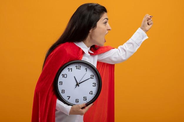 Przekonana, młoda superwoman stojąca w widoku profilu, trzymając zegar podnosząc pięść w górę, patrząc prosto na białym tle na pomarańczowej ścianie